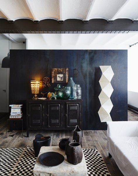 A vintage console and a Noguchi floor lamp sit in front of an oxidized metal partition.