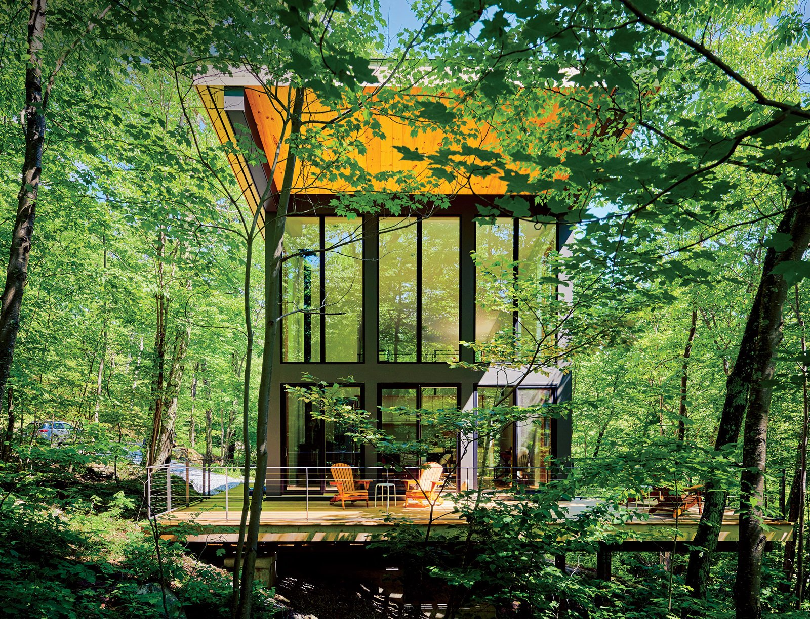 """Exterior, Cabin Building Type, House Building Type, Metal Siding Material, and Glass Siding Material A cantilevered cabin designed by R D Gentzler blends into the forest, even as it hovers above a 20-foot drop-off. Its south face is almost entirely glass, but a roof canopy limits solar gain. """"We sit on the deck all afternoon watching the trees, and the time just flies by,"""" says resident Maricela Salas.  Photo 36 of 101 in 101 Best Modern Cabins"""
