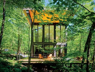 "A cantilevered cabin designed by R D Gentzler blends into the forest, even as it hovers above a 20-foot drop-off. Its south face is almost entirely glass, but a roof canopy limits solar gain. ""We sit on the deck all afternoon watching the trees, and the time just flies by,"" says resident Maricela Salas."