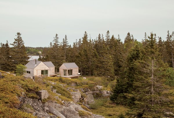On a sloping site near a defunct rock quarry on the remote lobster-fishing island of Vinalhaven, Maine, a three-part summer home overlooks a framed view of Penobscot Bay. Working around the site's unique topography, design-build firm GO Logic created each structure at varying elevations.