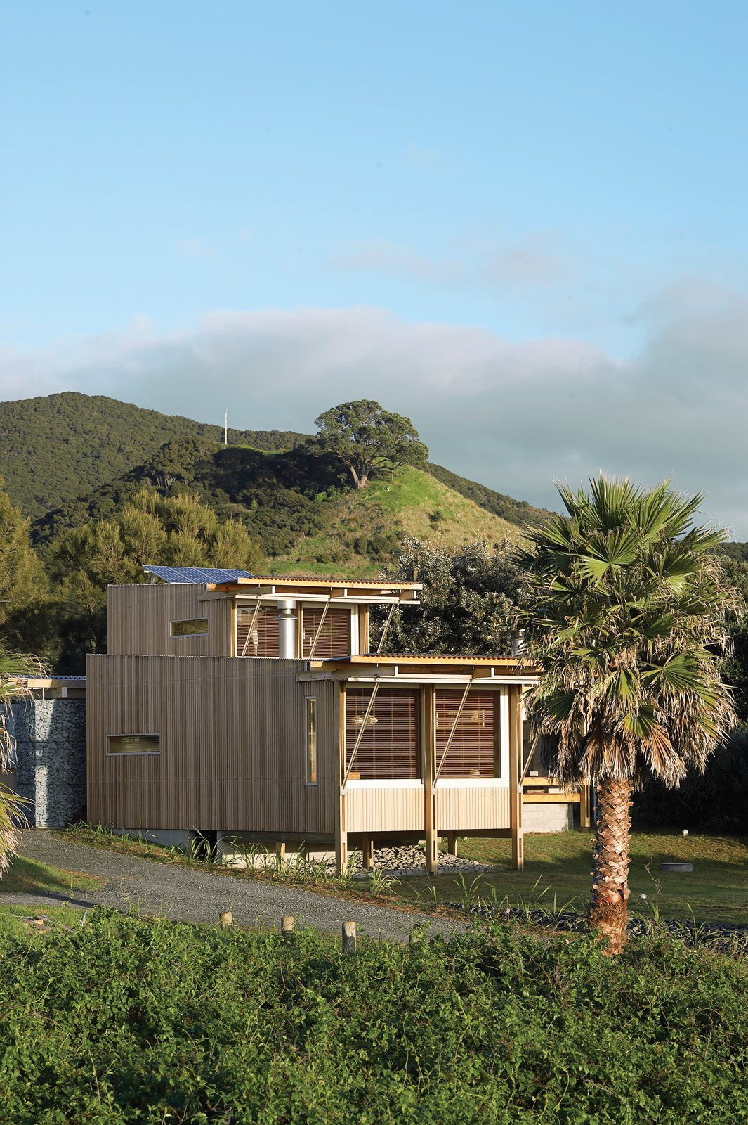 Exterior, House Building Type, Wood Siding Material, and Flat RoofLine The cedar-clad home designed by Herbst Architects faces the Pacific Ocean, tucked behind sand dunes from the sparsely populated Medlands Beach.  Best Photos from New Zealand Vacation Home Designed Completely Off the Grid