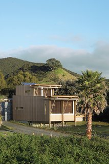 Designed for off-grid functionality out of necessity, the self-sufficient bach that Herbst Architects designed for their friend is a stellar getaway on New Zealand's Great Barrier Island. Clad in cedar, the modestly sized abode embraces outdoor living and views of the Pacific Ocean.