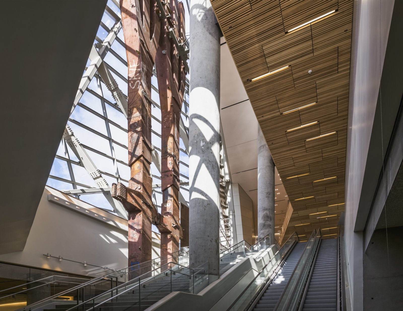 """The pavilion is outfitted with materials, including ash slats on the ceiling, that Craig Dykers, founding partner at Snøhetta, says were chosen to """"provide a sense of comfort as this is a site filled with a great deal of anxiety."""" At left are a pair of """"trident"""" columns that survived the collapse of the North Tower of the World Trade Center. Photo courtesy of Snøhetta.  Photo 3 of 14 in At Ground Zero Bedrock, the 9/11 Museum Prepares for Visitors"""