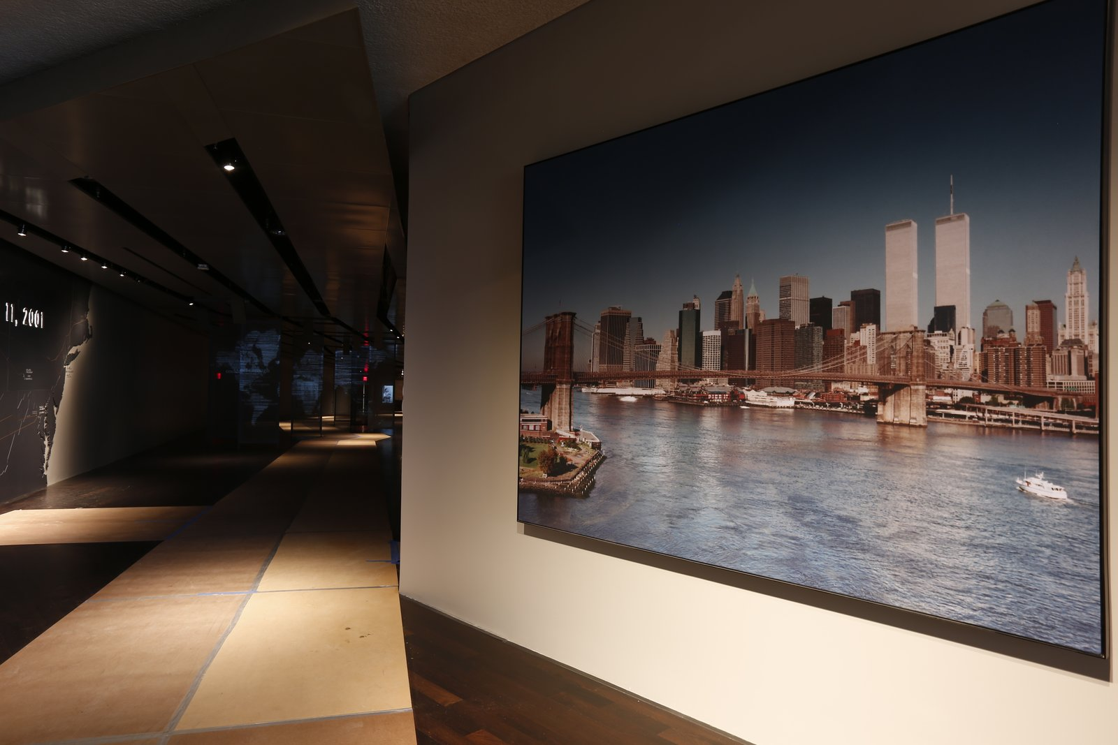"""Visitors will pass this photograph of the World Trade Center, taken at 8:30 a.m. on September 11, 2001, as they begin to follow the """"ribbon"""" from the concourse level down to the exhibits at bedrock level. Photo by Jin Lee.  Photo 5 of 14 in At Ground Zero Bedrock, the 9/11 Museum Prepares for Visitors"""