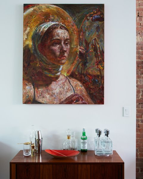 The moody painting by artist Victor Wang complements the exposed brick wall and the muted colors of the bar cabinet. Photo by Tara Donne.