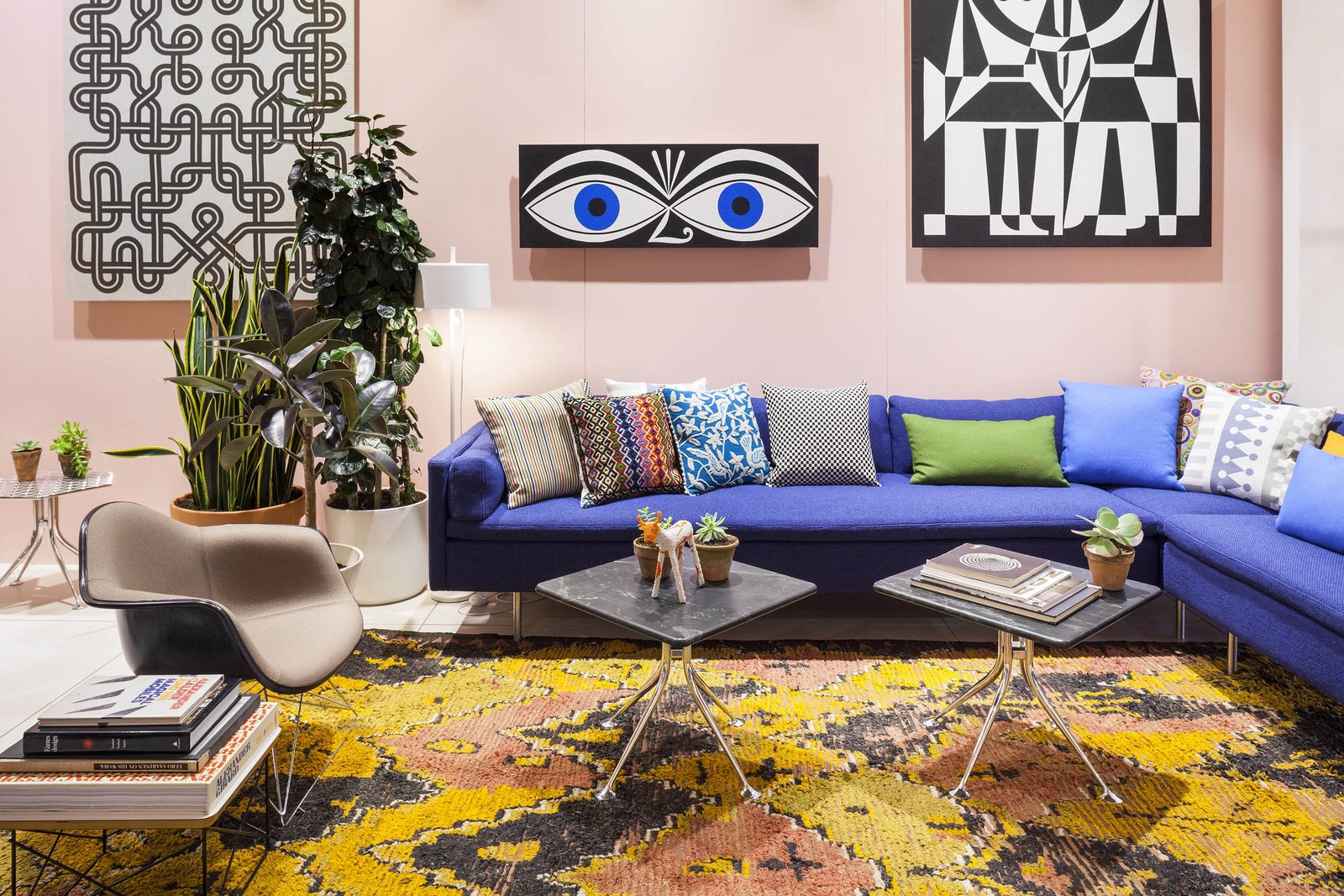 """A sitting room in the back is outfitted with marble-topped Splayed Leg tables (foreground), one of the Girard pieces that Herman Miller is reintroducing. Three of Girard's screen-printed environmental enrichment panels—from left, """"Knot,"""" """"Eyes,"""" and """"Black and White""""—hang on the wall above the couch. Photo courtesy of Herman Miller.  Photo 4 of 5 in Alexander Girard: An Uncommon Vision"""