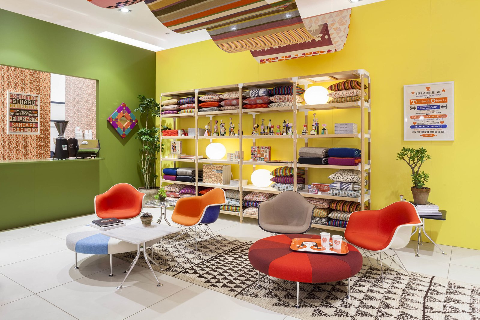 Girard designed the Color Wheel ottomans, shown here, for Braniff International Airways as part of a top-to-bottom rebranding effort in 1965. A reproduction of a poster that Girard designed for his Textiles & Objects store, hangs on the wall at right. Photo courtesy of Herman Miller.  Photo 3 of 5 in Alexander Girard: An Uncommon Vision