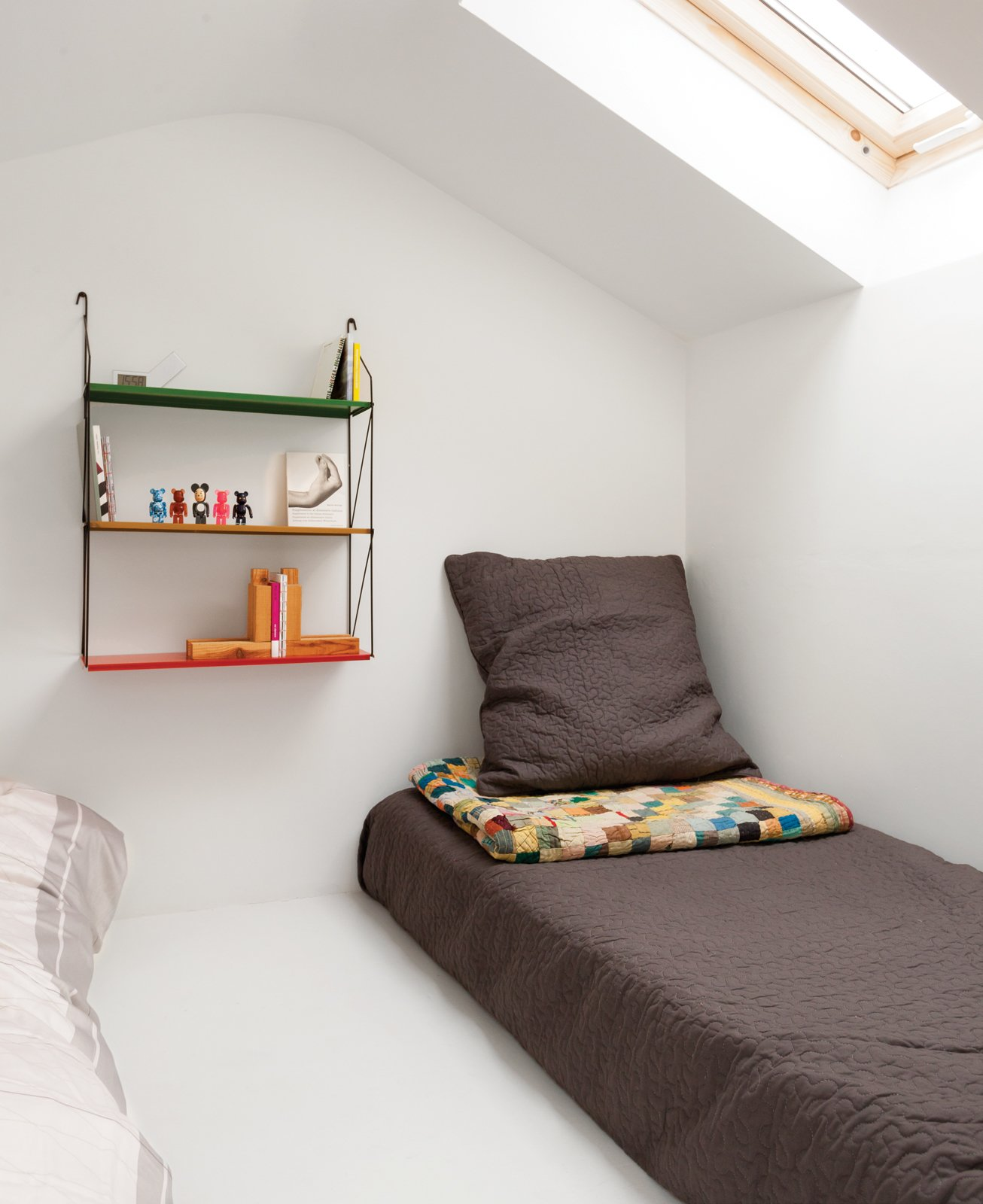 A colorful shelf offers bedside storage in a London guesthouse.  Shelves