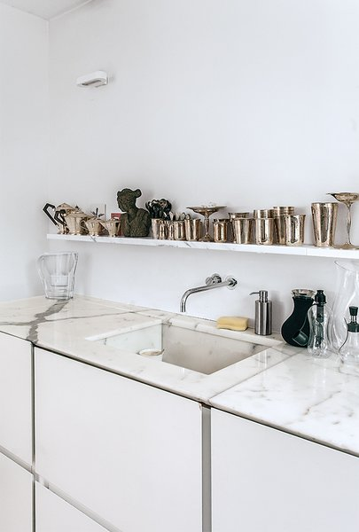 Molineus designed all of the storage units in the apartment, including the lacquered medium-density fiberboard cabinets under the kitchen sink, which is outfitted with a Vola faucet.