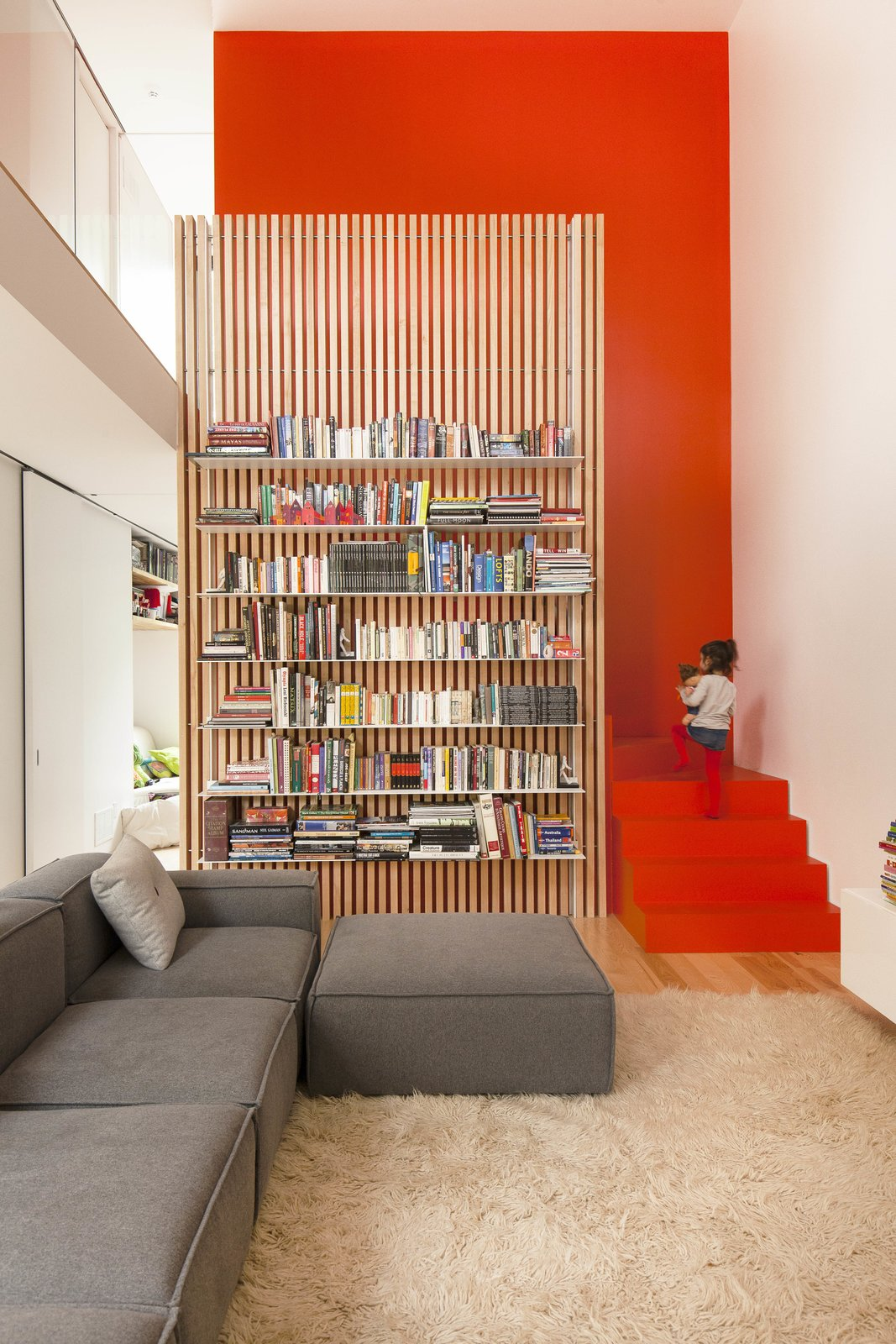 Living Room, Sectional, and Bookcase The stairs are partically hidden behind a slatted ash screen that supports steel bookshelves.  190+ Best Modern Staircase Ideas from A Transformative Duplex Renovation in Montreal