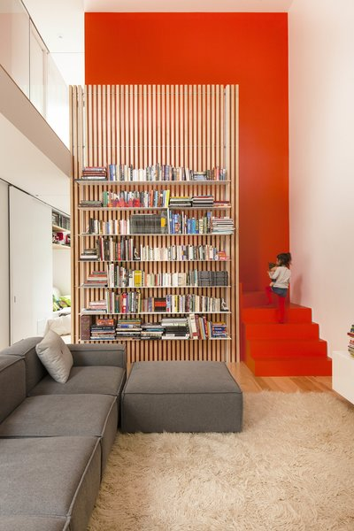 The stairs are partically hidden behind a slatted ash screen that supports steel bookshelves.