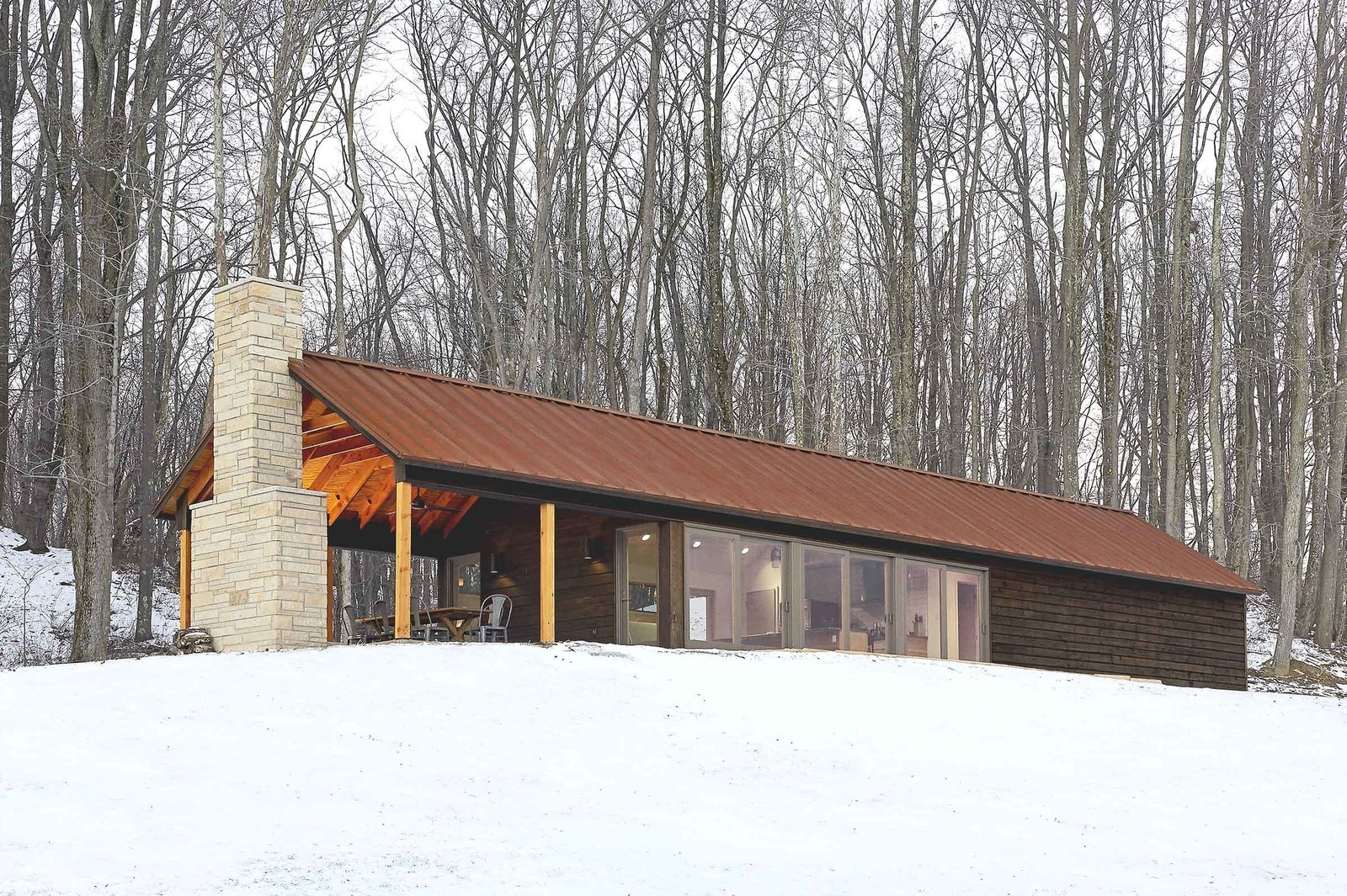 The retreat's southern exposure maximizes sunlight with 24 feet of floor-to-ceiling windows. The sun's warmth is absorbed and stored in the concrete floor, keeping the interior warm. Combined with thickly insulated walls, the cabin requires little additional energy, and has gone up to three days in winter without any electrical heating.  Off-Grid Retreat by Zachary Edelson from Modern Gabled Cabins