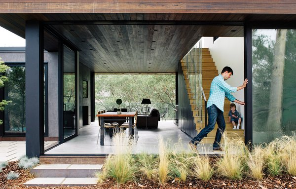 With his son, William, watching, architect Noah Walker tries out the floor-to-ceiling Schüco glass doors he integrated into a guesthouse he designed off an existing barn for Nathan Frankel, an amateur violinist, in Beverly Hills, California. The new portion features an open living-dining area. See more glass houses we love!