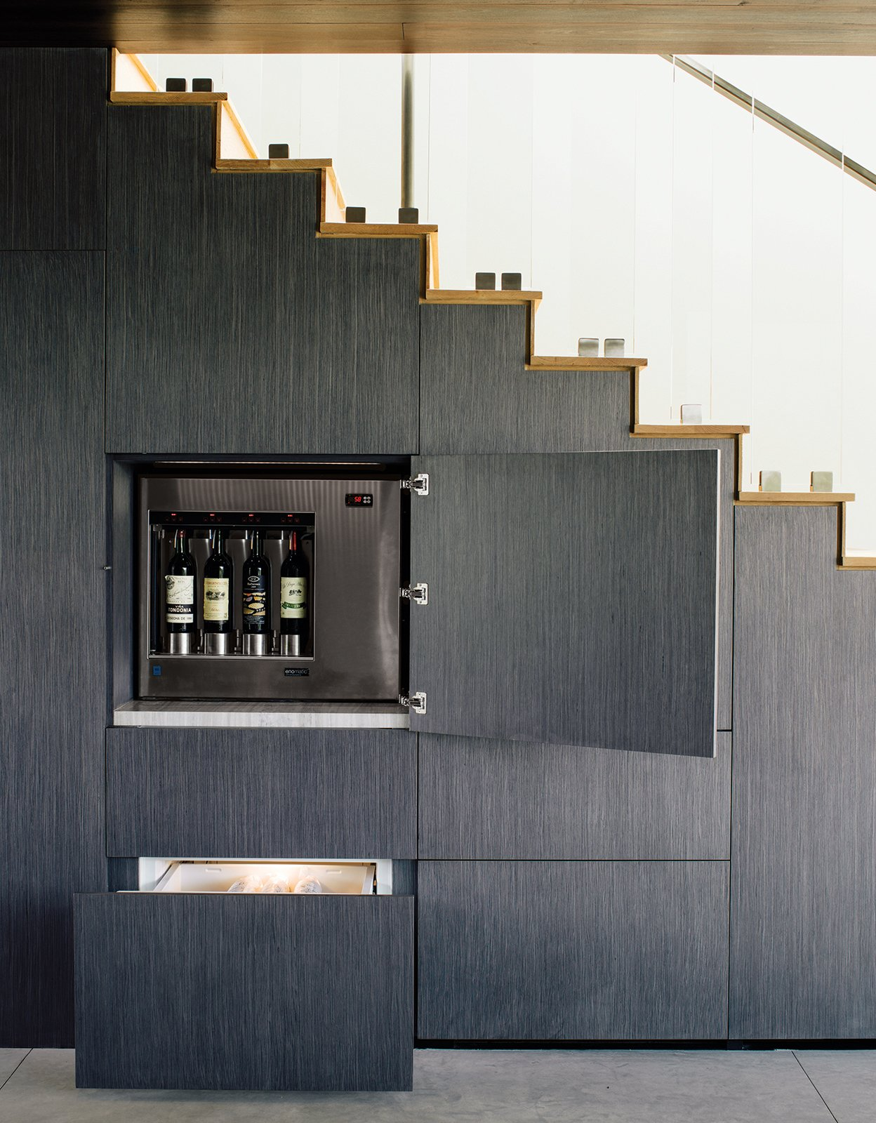 Staircase and Wood Tread The wall beneath the stairs holds hidden storage, including an Enomatic wine dispenser and Sub-Zero refrigerated drawers.  Storage from Modern Home Designed for Live Music in Beverly Hills