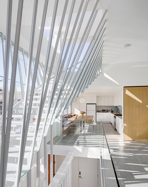 The dramatic staircase in architect Dom Dimster's Southern California home is made from T- and L-profile steel, shelf board, glass panels, and plate steel. Electric shades on the outside of the house keep the sun from penetrating the glass wall of the staircase and overheating the interior.