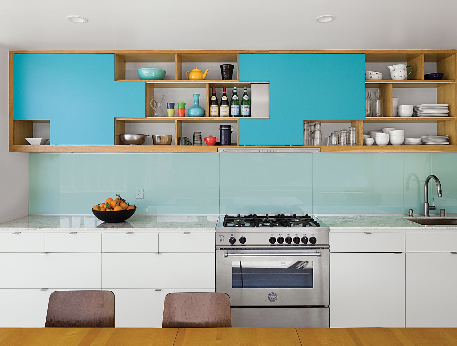 Kitchen, Colorful Cabinet, Range, Undermount Sink, Recessed Lighting, Open Cabinet, White Cabinet, and Glass Tile Backsplashe Modern cabinet finger pulls in a more bright and shiny chrome dot the drawers in this sleek kitchen in Venice, California.  Photo 9 of 10 in 10 Open Kitchen Solutions That Will Get Things Cooking from A Minimalist Duplex in Venice, California