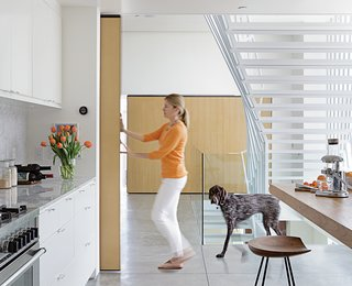 """A nine-foot-tall door covered with quarter-inch white oak slides along a ceiling rail and can be moved with just a finger to close off Don and Lisa's kitchen or bedroom. Made of wood and metal, and welded onsite, the door moves along 400-pound-capacity rollers by McMaster-Carr. A matching sliding door opposite hides a storage area. """"Because of their size, the doors had to be made inside,"""" says Don, who did the job himself. mcmaster.com"""