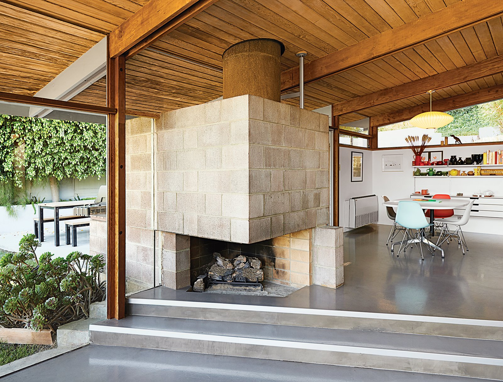 Living, Pendant, Chair, Wood Burning, Corner, Table, and Concrete The dining area features a distinctive cinder block fireplace. Molded plastic side chairs are arranged around a Segmented Base table, all by Charles and Ray Eames for Herman Miller. The space is illuminated by a Saucer pendant lamp by George Nelson from Modernica.  Best Living Corner Chair Photos from A Midcentury Home Keeps the History Alive