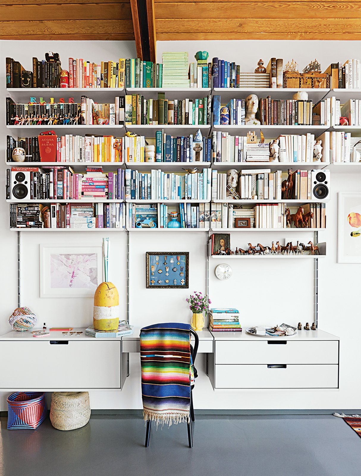 A 606 Universal Shelving System by Dieter Rams for Vitsœ dominates one end of the living room.  Home Libraries that Take Book Storage to the Next Level by Diana Budds from A Midcentury Home Keeps the History Alive