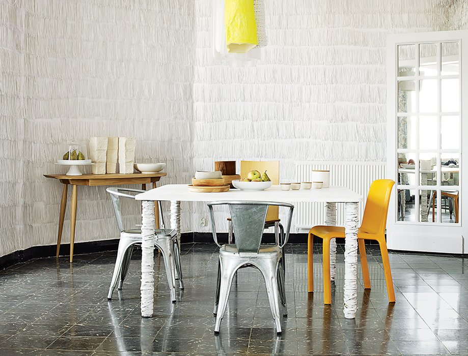 Pedrali's orange Frida 752 chair, two metal Tolix Marais chairs, and Philippe Starck's Olly Tango seat surround a dining table that resident Pierre Pozzi wrapped in paper.  Photo 10 of 10 in 10 Modern Renovations to Homes in Spain from An Artist's Dining Room in Valencia Has Fringed Paper Walls
