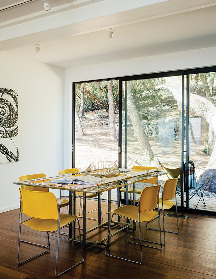 """Dining Room, Chair, Table, and Medium Hardwood Floor David Rowland stacking chairs join a 1970s Italian glass-and-steel table in the dining room. The daughter loves being able to stop in to visit. """"I'm over there ten times a day. It's brought me such peace.""""  Beautiful from This Northern California Prefab Gets a Dose of Universal Design"""