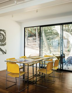 """David Rowland stacking chairs join a 1970s Italian glass-and-steel table in the dining room. The daughter loves being able to stop in to visit. """"I'm over there ten times a day. It's brought me such peace."""""""