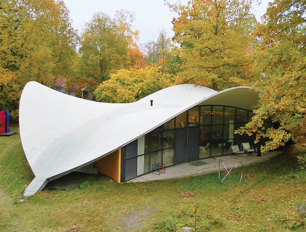 """The 1968 house's shape—a rounded triangle topped with a sweeping concrete roofline that suggests a helmet as it rises above huge banks of windows—lends itself totally to Kukkapuro's philosophy. """"It is a structure in waiting, prone to change as the landscape around it—not yet a form, rather a possibility,"""" he says. """"It changes in harmony with the seasons and the moods of its inhabitants."""""""