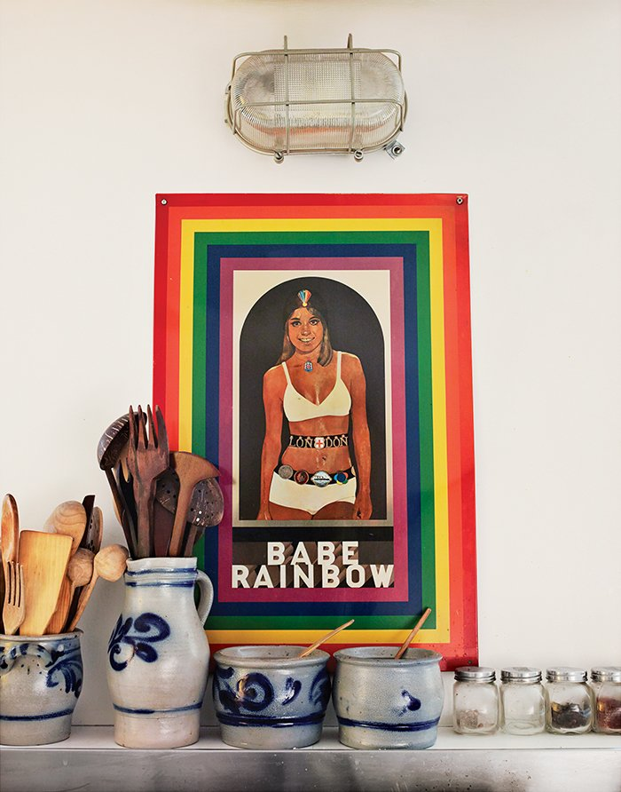 British Pop artist Peter Blake's 1968 Babe Rainbow print hangs amid pottery and kitchen utensils on Aulenti's stove in her tiny galley kitchen.  Photo 4 of 6 in Elegant Milan Home of Designer Gae Aulenti