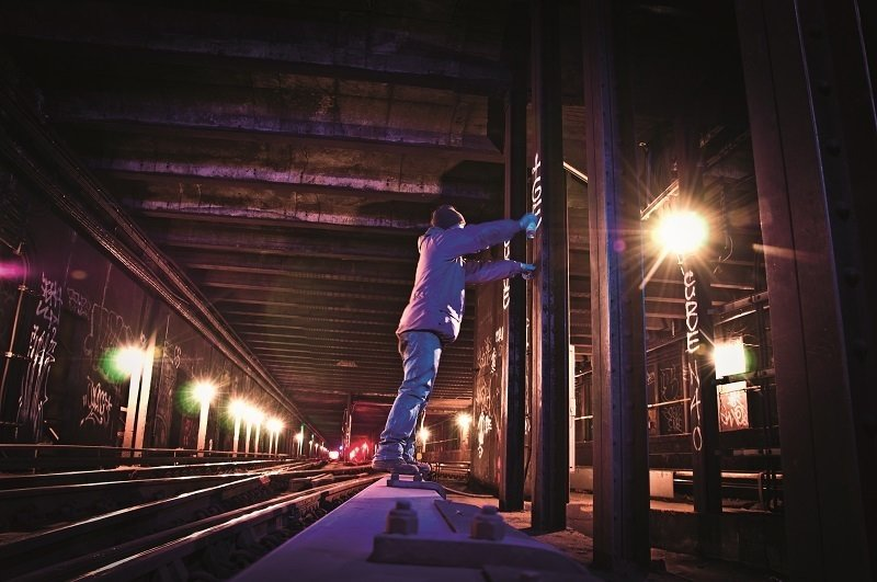 Graffiti artist standing on a wood covering over the third rail. Photo courtesy Matt Litwack.  Photo 2 of 10 in Beneath the Streets: Photos of New York's Secret Underground