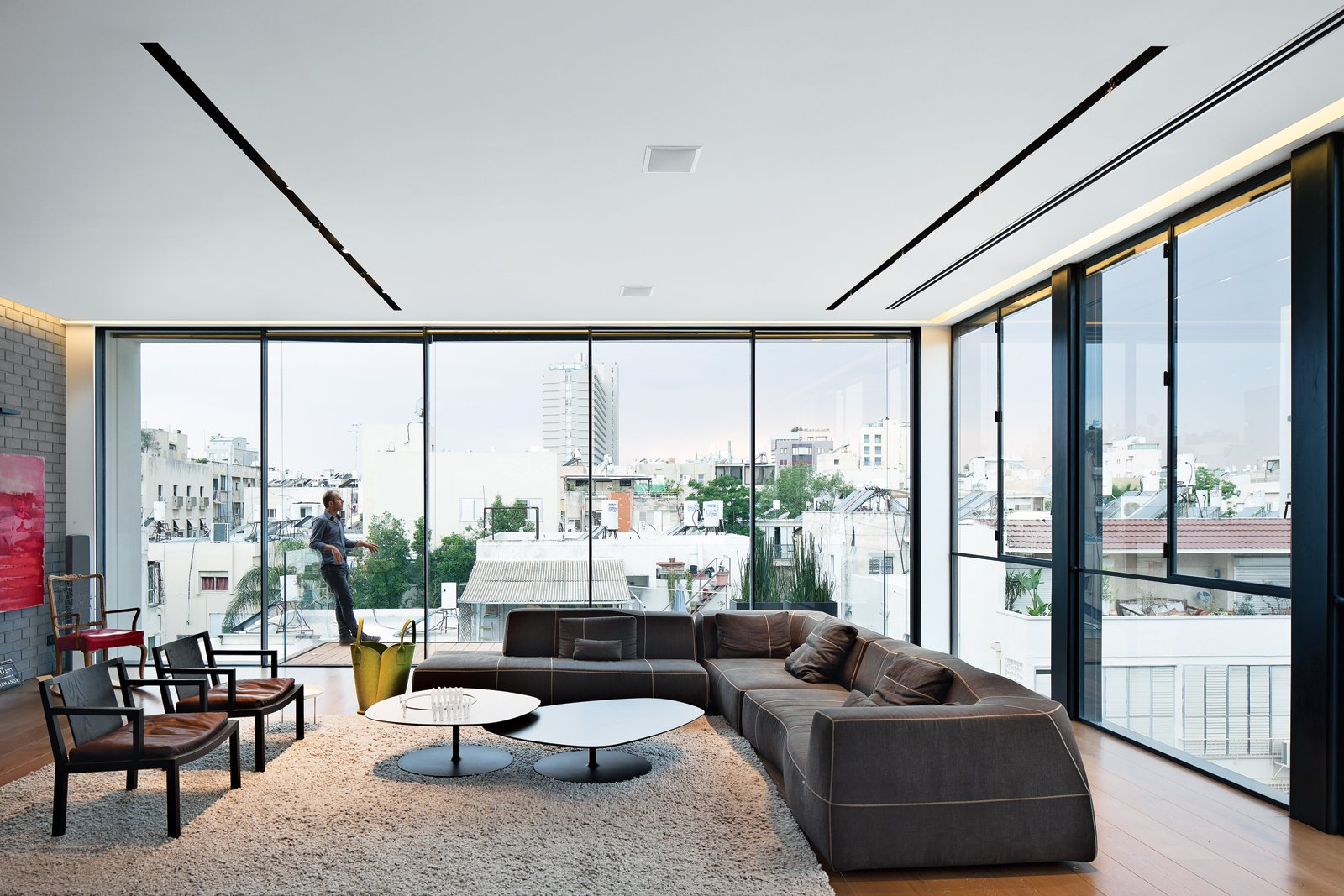 Living Room, Sectional, Light Hardwood Floor, Rug Floor, Chair, and Coffee Tables The living room features stunning views of the city, a Bend sofa and Phoenix coffee tables, both by Patricia Urquiola for B&B Italia and Moroso, respectively, and two Gray armchairs by Piero Lissoni for Living Divani.  20 Homes with Inspiring use of Glass by Diana Budds from Modern High-Rise Town House in Tel Aviv