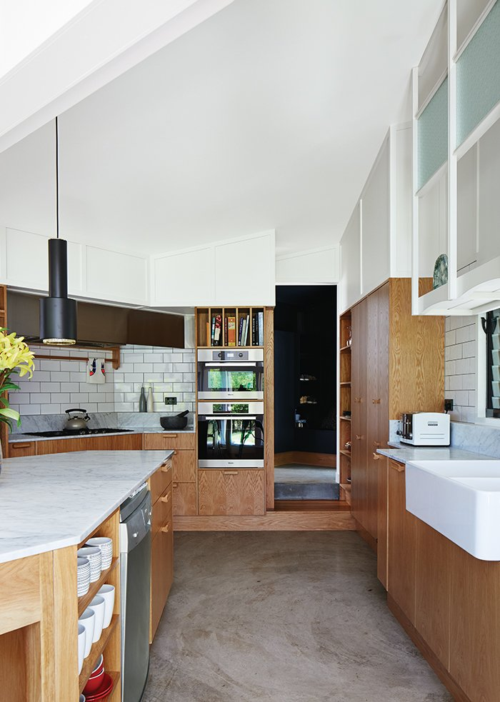 Kitchen, Marble Counter, and Wood Cabinet Brisbane-based studio Owen and Vokes and Peters designed a modern kitchen addition for a traditional Queensland-style timber house. Glossy Vogue Ghiaccio kitchen tiles set off custom cabinetry built by Cooroy Joinery & Woodworks using American oak veneer and Centor doors. The dishwasher is by AEG.  Photo 3 of 5 in This Kitchen Brings It All Together