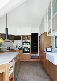 Brisbane-based studio Owen and Vokes and Peters designed a modern kitchen addition for a traditional Queensland-style timber house. Glossy Vogue Ghiaccio kitchen tiles set off custom cabinetry built by Cooroy Joinery & Woodworks using American oak veneer and Centor doors. The dishwasher is by AEG.