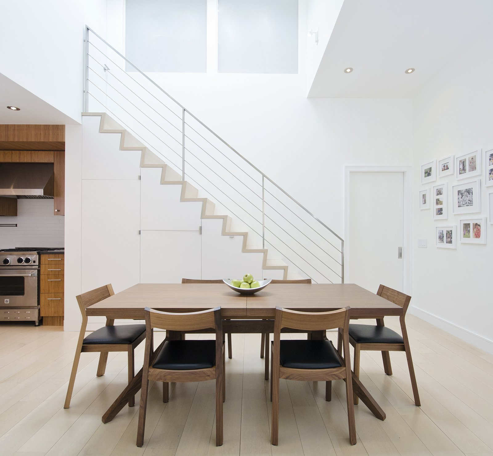 """""""We refaced some of the kitchen cabinets and altered the staircase a little bit,"""" Miller says. The new staircase features a design that accommodates storage for a microwave and pantry items. A warm wood dining table by Matthew Hilton and Profile chairs from Design Within Reach stand out against the white walls and pale flooring.  A Renovated Tribeca Loft with a Modern Aesthetic by Monique Valeris"""