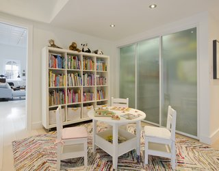 A playroom kitted out with a table and chairs from is situated between the kids' rooms in what was formerly an underutilized passageway.