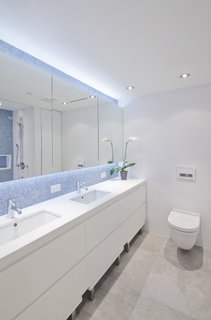 "In addition to a playroom, the children share a bathroom. ""In a kids' bathroom, it's nice to have a little bit more fun,"" Miller says. ""The penny tiles are really nice because they are really inexpensive and have a nice blue delicateness to them."" A neutral palette of whites and grays is used throughout the rest of the space to make the blue penny tiles stand out. Footstools are nestled underneath the cabinets so the kids can access the sink easily."