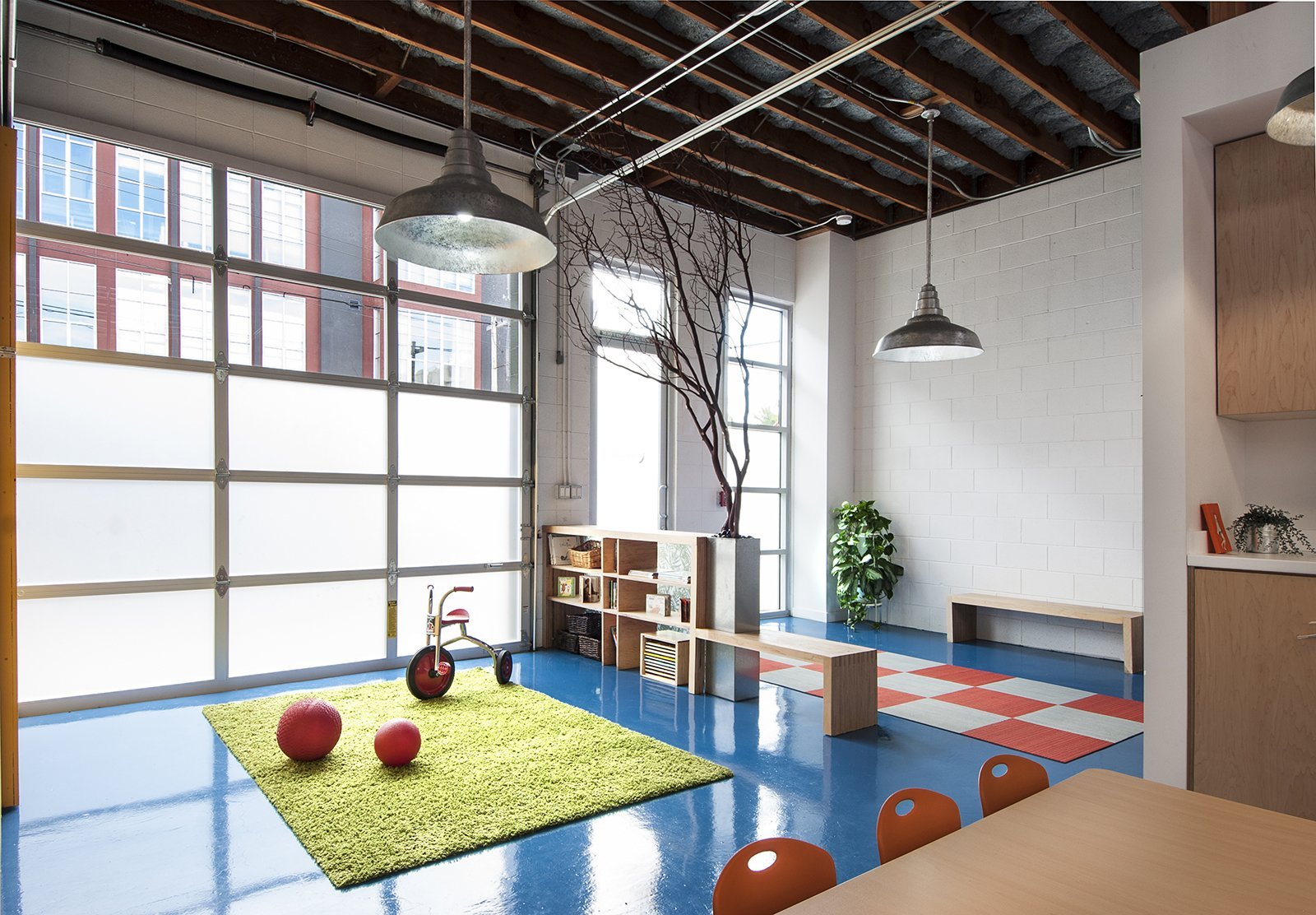 """Kids Room """"There is a triangle in projects between budget schedule and design,"""" Curtiss says. """"The common wisdom is you can hit any two but hitting all three is hard.  We tried to hit all three."""" The raw space featured concrete floors and since it was formerly industrial, had oil spills on the slab. To create a floor that was safe for the kids, Curtiss opted for an epoxy. """"Epoxy floors are used in hospitals and labs and are super easy to clean. We also knew it was an economical way to coat concrete."""" Custom colors are available, but for an extra charge. To rein in expenses, Curtiss chose a blue hue that's normally used for ADA striping.  Natural light floods the interior thanks to Solatubes. Barn lights from HiLite offer additional illumination. Curtiss left the Ultratouch blue denim insulation exposed in the ceiling. """"We asked the insulation supplier if we could check the denim batch colors,"""" she says. """"We didn't want black mixed in with the washed blue color. He thought we were crazy.""""  Photo 14 of 15 in Get Ready For July 4th With 15 Spaces That Rock Red, White, and Blue from A Modern Preschool in San Francisco"""