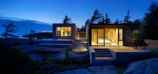 The SHIFT cottage on an island in the Georgian Bay, divided into two volumes, features a simple geomtric shape and knotty cedar cladding.