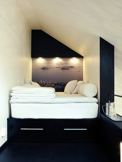 In this tiny sleeping loft is a platform bed with two drawers beneath it. In place of wallpaper, Schönning enlarged a photograph he snapped in Rio de Janeiro. The inset spotlights and a small shelf at the end of the bed offer light and additional storage.