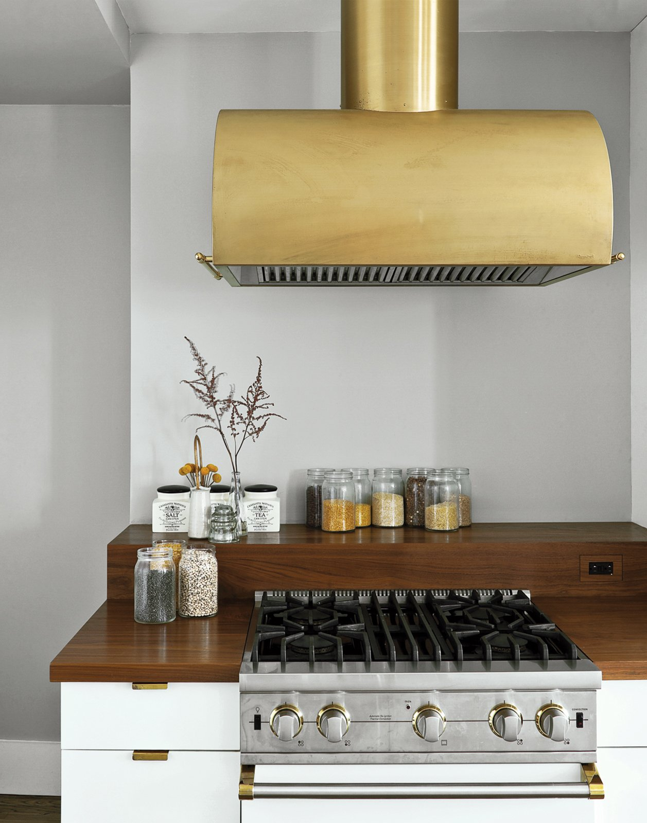 The Viking gas range is shown in Cotton White   and finished in polished brass details to match the   Workstead-designed hood.  Photo 9 of 12 in A Minimal Yet Mighty Brooklyn Apartment