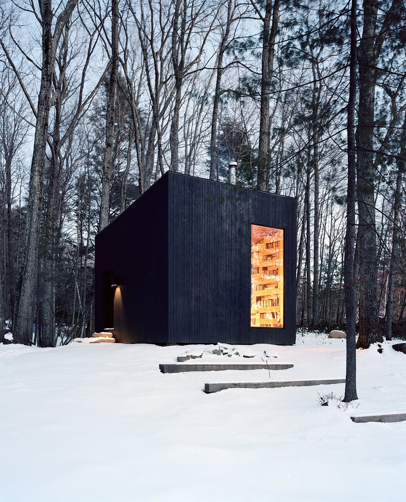 Exterior, Cabin Building Type, Wood Siding Material, Tiny Home Building Type, Metal Roof Material, Shed RoofLine, and Shed Building Type Jason and Suzanne Koxvold commissioned Studio Padron to design a 200-square-foot guesthouse on their Ellenville, New York, property. The geometric structure's dark cedar cladding contrasts with the inviting interior, which is heated by a cast-iron Jøtul stove. A layer of built-in bookshelves made from felled oak lumber also helps insulate the building in winter.
