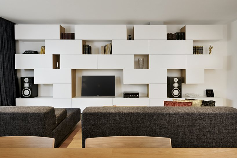 """Dragisic used basic materials and colors throughout the apartment: white for the custom shelving, charcoal gray for the sofa from Cor, and oak for the furniture and flooring. """"This approach allowed the residents the freedom of doing any additional decorations (art, colored cushions, carpets, accessories etc.) without disrupting the overall design-statement,"""" she says.  Storage by Dwell from A Compact Minimalist Apartment in Slovenia"""