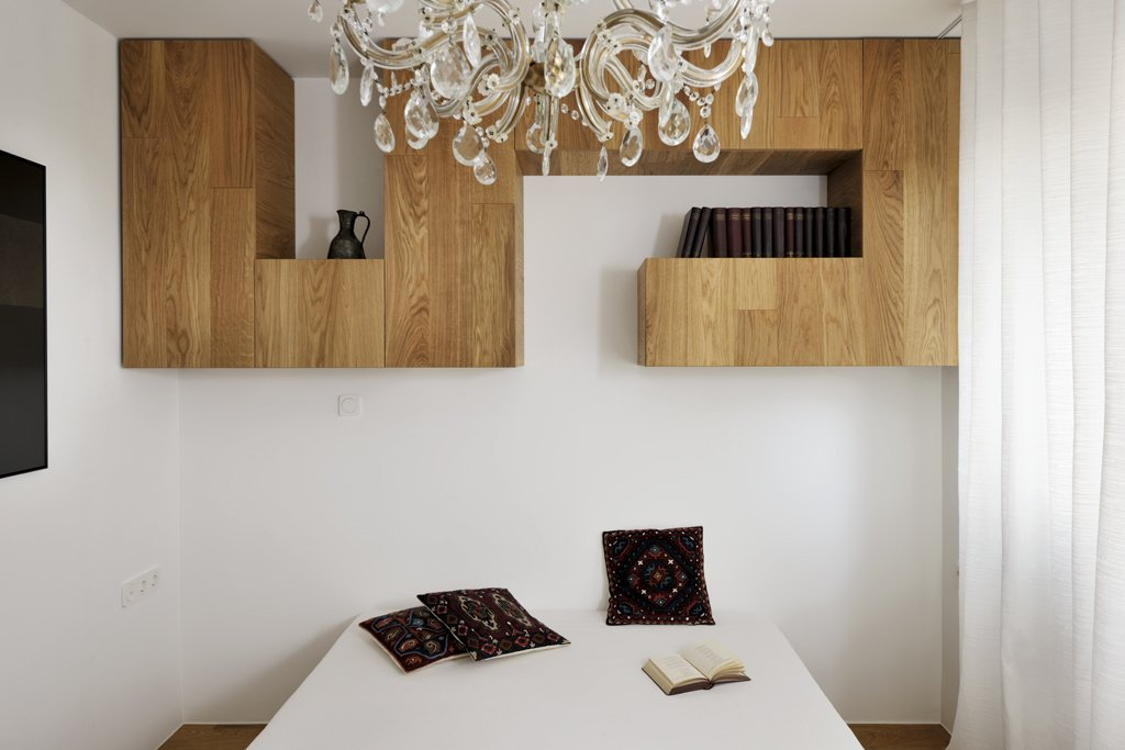 """""""The ceiling in the bedroom adorned with a crystal chandelier, which (along with the other vintage accessories) gives this residence a unique soul,"""" Dragisic says.  A Compact Minimalist Apartment in Slovenia by Diana Budds"""