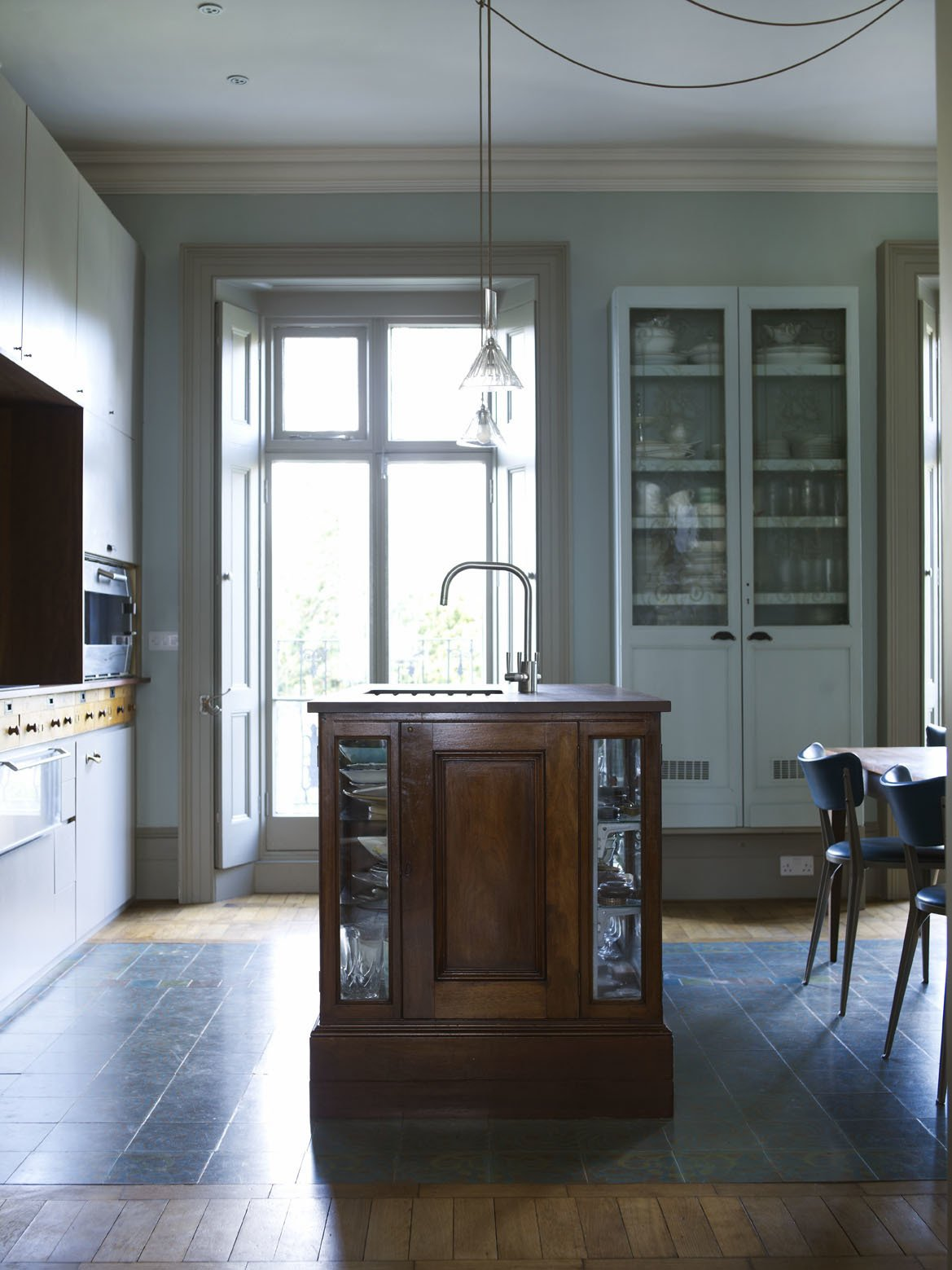 The kitchen island is a mahogany museum display case containing the clients' inherited snuff-box collection. Now topped with salvaged iroko hardwood from a school science laboratory, it has also been adapted to hold a sink and washer.  Photo 4 of 12 in A Gracious London Terrace House Is Reborn with Salvaged Materials