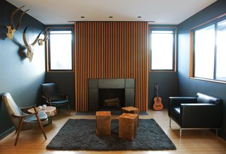 In Los Angeles, homeowner Bill Thompson warmed up his otherwise dark living room with a series of Douglas fir slats applied above the fireplace, as well as other wood accents throughout the room; the slats provide both texture and pattern to the fireplace, acting as a focal point and emphasizing the space's vertical height.