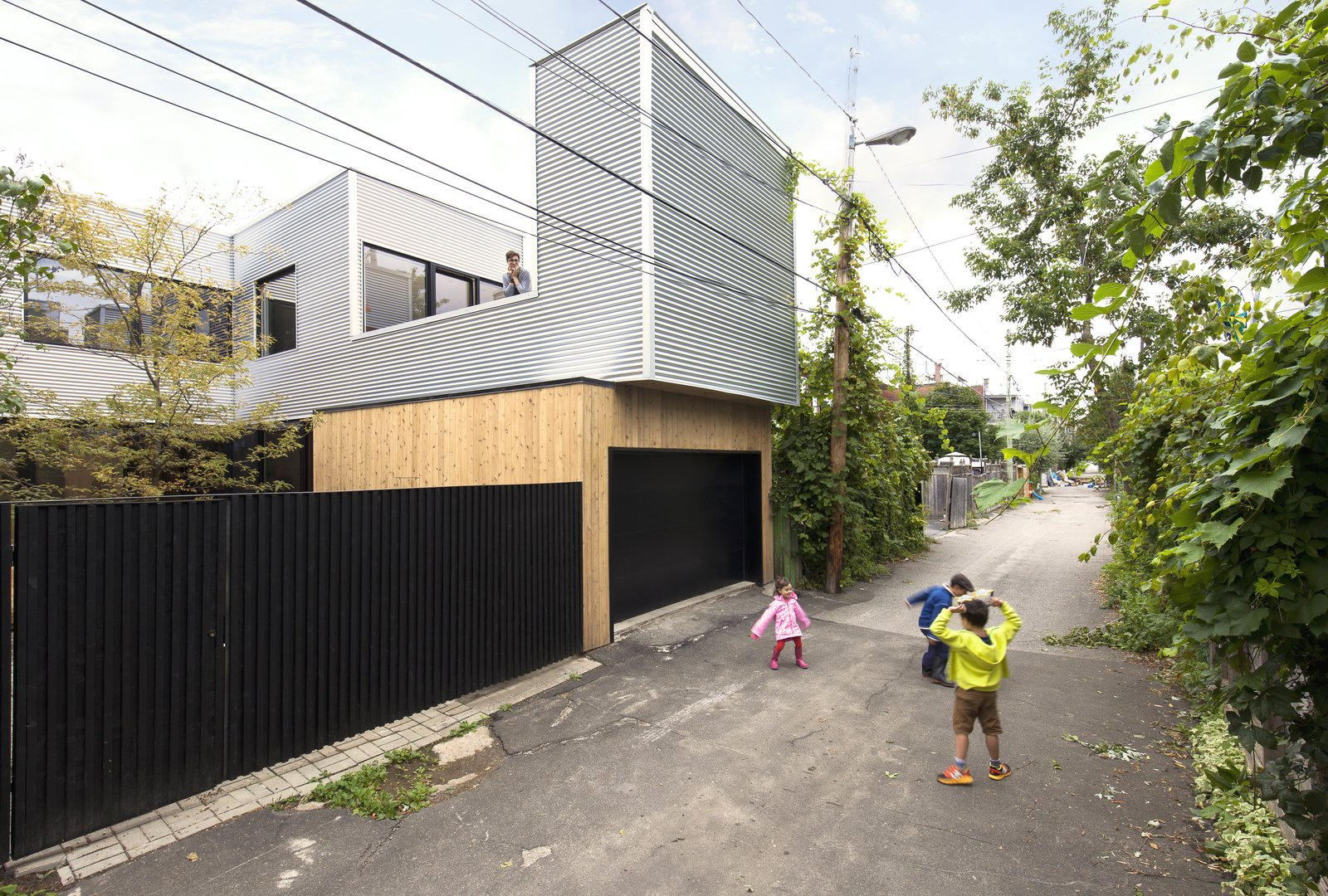 The architects cut away a section of the second floor to make room for a patio. The exterior has been clad in corrugated galvanized steel and cedar planks.  Best Photos from A Transformative Duplex Renovation in Montreal