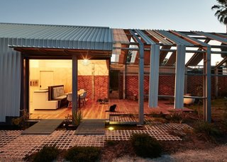A steel-framed, bi-fold door system by Skyrange Engineering separates the edge of the house from the outdoor area.