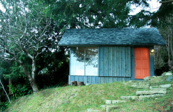 A recycled barndoor track and wheels affords privacy behind a siding covered panel.