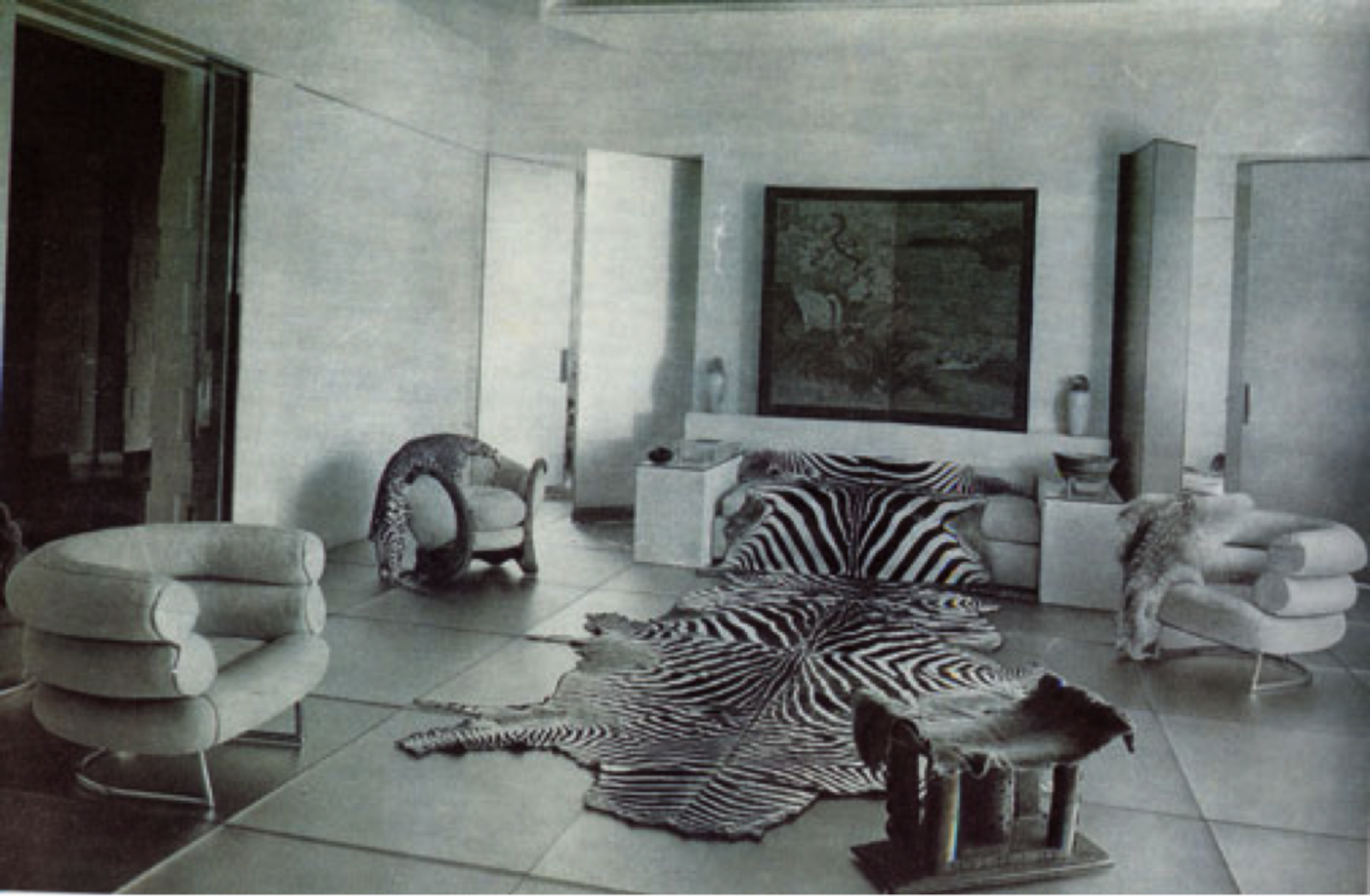 The Rue de Bonaparte apartment, which features the Bibendum chairs along with a collection of striking animal hide blankets and rugs, provides a sense of the modernist atmosphere within which the designer worked. White walls and open spaces, as well as a clear geometricity in the floor tiles and organization of the room, give the apartment a Le Corbusier-like airiness. This tone is complimented by Gray's interest in femininity and comfort, which she incorporates through natural materials and delicate lines, differentiating her from her contemporaries.  Photo 5 of 6 in Design Icon: Eileen Gray