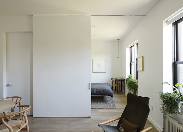 A seamless sliding door by CS For Doors—accented by Mockett hardware—separates the master bedroom from the living room and doubles as a backdrop for a projector.
