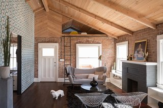 "In the living room, Busick left the original brick walls and tongue-and-groove wood ceiling exposed, while he refinished the white oak flooring with a walnut stain. ""We edited the newer renovations to the historic home down to the fundamental elements,"" he explains. A gray Delos Sofa by Control Brand sits cozily in front of a window."